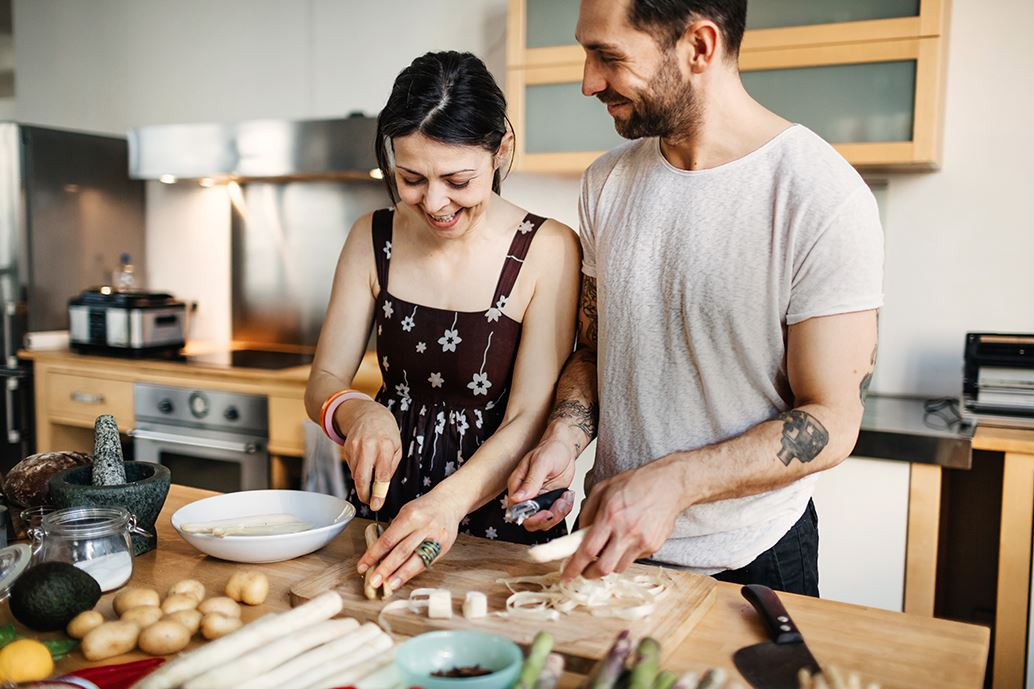 Happy couple preparing food in kitchen
