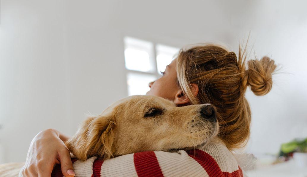 Jonge vrouw kroelt met haar hond