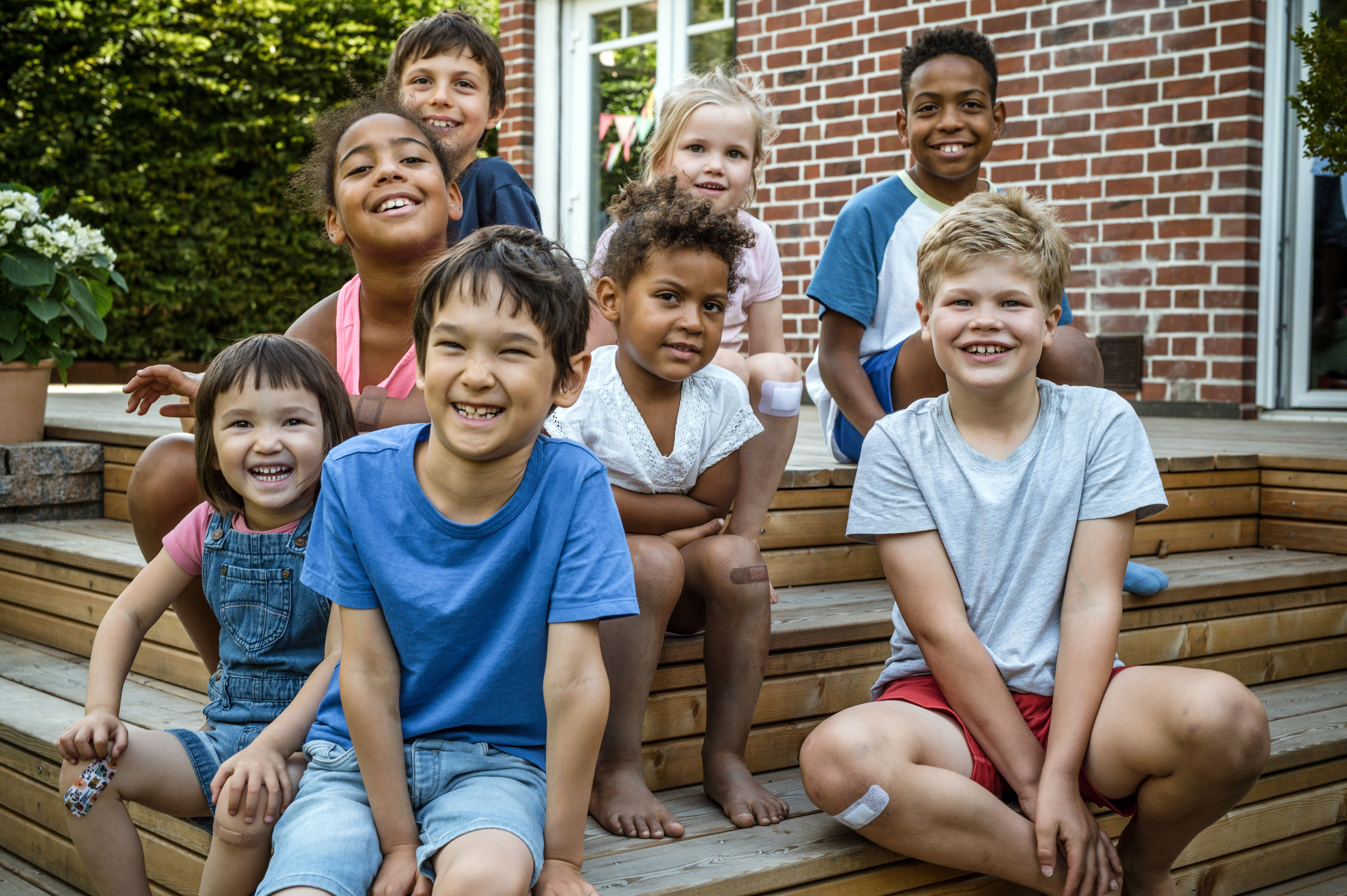 Eight smiling children sitting on some wooden steps.
